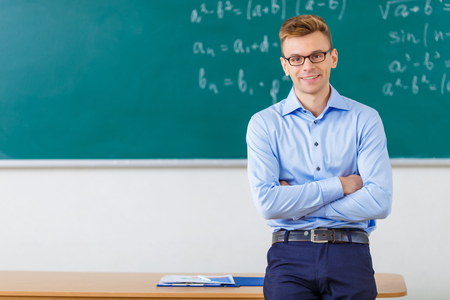 Handsome young college professor smiles charmingly while folding his arms and leaning against the desk.
