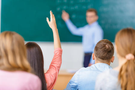 student studying: Female young student in a group raises her arm in order to answer the question.