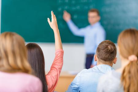 Nő fiatal diák egy csoportban emeli a karját, hogy válaszoljon a kérdésre.