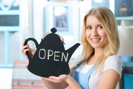 agreeable: Cheerful agreeable smiling waitress holding notice and waiting for guests while working  in the cafe