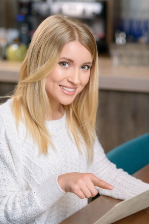 appealing: Pleasant content appealing smiling girl sitting in the cafe and holding menu while having lunch