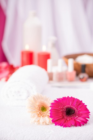 Nice colorful flowers lying on the table of beauty salon with nail polishes standing in the background
