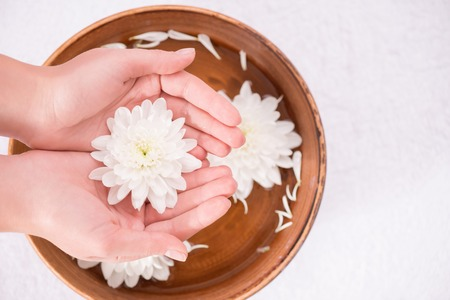 cuticle pusher: Top view of white beautiful flower in hands of woman holding it on the spa bowl with water