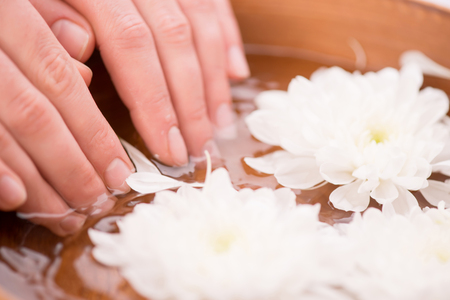 cuticle pusher: Close up of beautiful tender hands of woman holding her fingers in the spa bowl with water while receiving beauty therapy Stock Photo