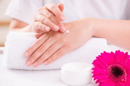 cuticle pusher: Close up of tender young hands of woman holding them on the towel and covering with cream while making massage Stock Photo