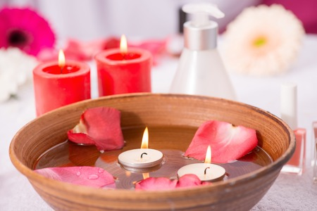 cuticle pusher: Close up of spa bowl with water and rose petals standing on the table near candles and bottle of cream
