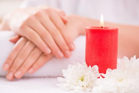 cuticle pusher: Close up of burning candle and white flower on the table with tender hands lying on the towel in the background