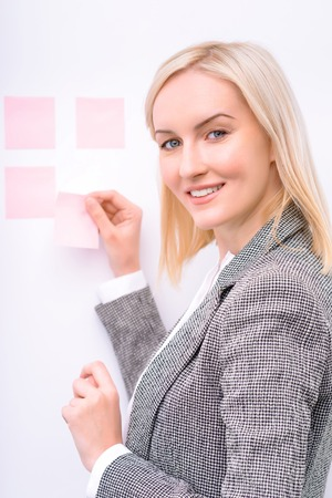 vivacious: Waist up of pleasant smiling vivacious businesswoman holding sticker and gluing it on the wall while being involved in work Stock Photo