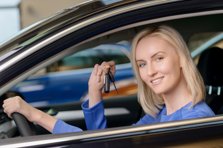 confident woman: Young attractive client demonstrating a car key while sitting inside her brand new vehicle.