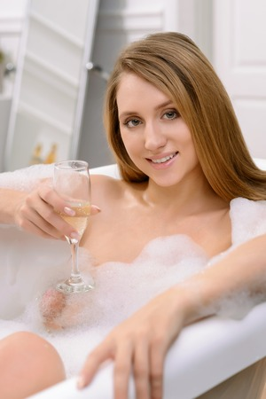 voluptuosa: Agradable deleitó sonriente mujer voluptuosa de tomar un baño y la celebración de vidrio, mientras que beber champán.