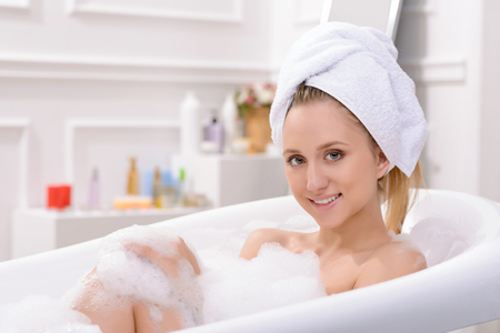 fetching: Nice positive cheerful fetching woman lying in water and feeling content while having a  bath