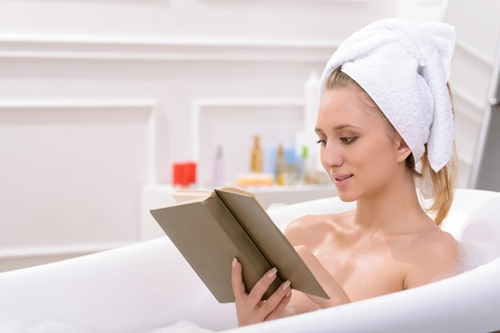 appealing: Nice appealing young woman lying in the bath and reading book while taking care of herself