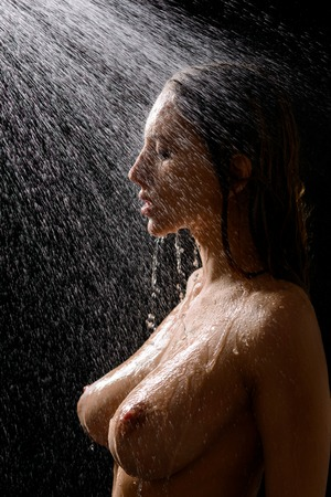 half nude: Pleasant voluptuous seductive nude girl standing half turned and raking a shower while feeling delighted