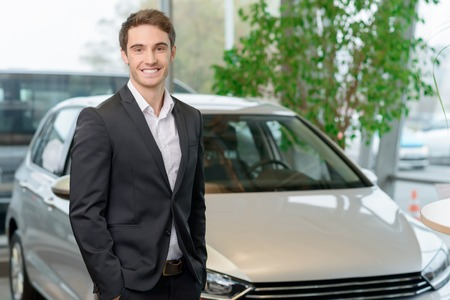 buoyant: Good-looking young man is smiling brightly while posing in front of a car.