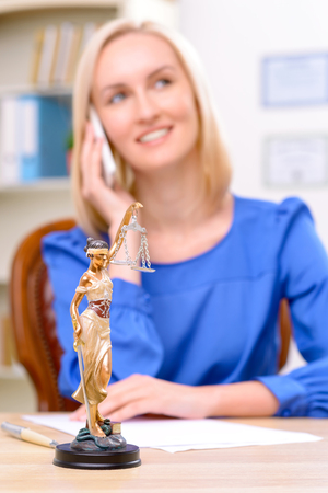 female lawyer: Close up of symbol of justice standing on the table with professional female lawyer sitting in the background and having conversation on cell phone Stock Photo