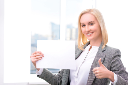 feeling up: Positive content smiling businesswoman holding  sheet of paper and thumbing up while feeling glad
