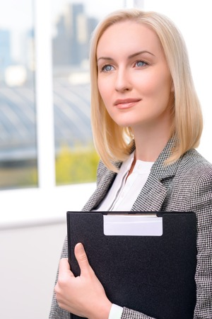 looking aside: Pleasant beautiful confident businesswoman holding folder and looking aside while doing her work