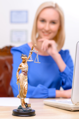 female lawyer: Close up of symbol of justice standing on the table with positive confident professional female lawyer sitting at the table Stock Photo