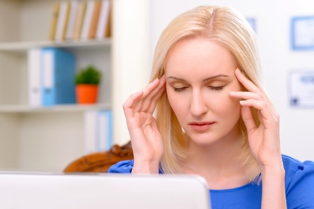 female lawyer: Close up of gloomy professional female lawyer sitting at the table and doing her job while feeling ache in head