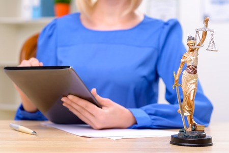 female lawyer: Close up of symbol of justice standing on the table with professional female lawyer sitting in the background and holding tablet