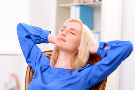 female lawyer: Close up of pleasant professional delighted female lawyer stretching in the arm chair and closing her eyes while relaxing Stock Photo