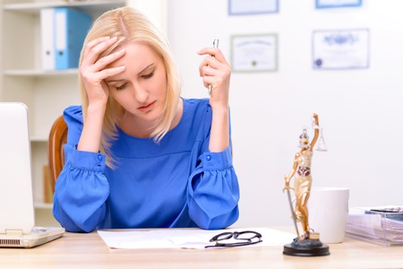 female lawyer: Much work  to do. Puzzled professional female lawyer sitting at the table  holding her head with hand while solving the problems at work Stock Photo