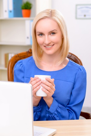 female lawyer: Pleasant content charming female lawyer sitting at the table and holding cup while drinking tea