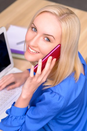 female lawyer: Top view of vivacious smiling professional female lawyer holding mobile phone and having conversation while sitting at the table Stock Photo