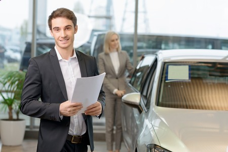 salesperson: Handsome young male salesperson holding papers while his customer is observing the car.