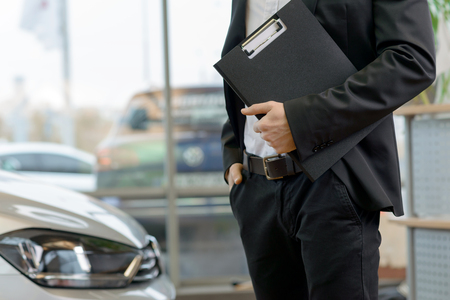 salesperson: Young male salesperson is standing beside the car and holding a clipboard. Stock Photo