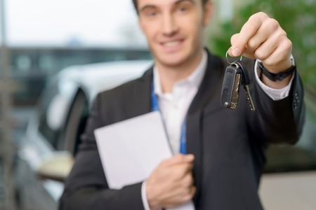 salesperson: Young successful salesperson is offering car keys to a client after closing the deal. Stock Photo