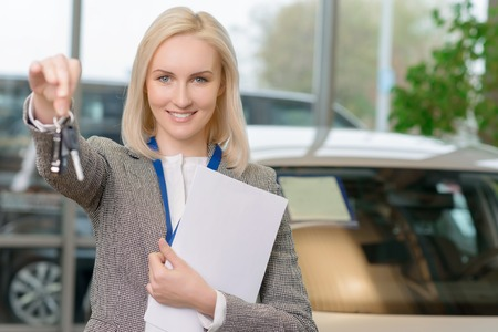 salesperson: Young female salesperson is offering car keys to a client after closing the deal.
