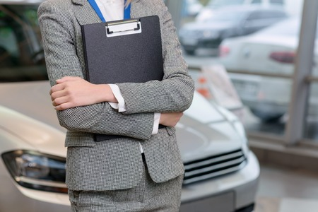 Young female salesperson is standing beside the car and holding a clipboard.