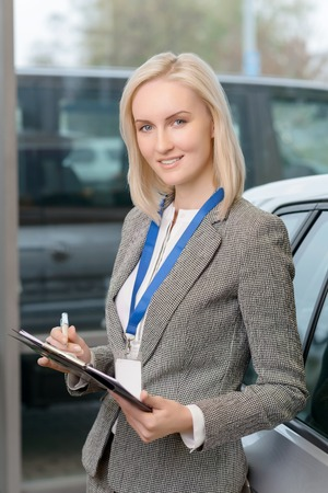 salesperson: Young female salesperson is standing beside the car and working with clipboard. Stock Photo