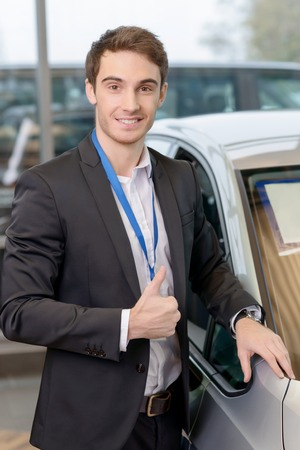 buoyant: Young handsome sales representative is showing thumbs up while presenting selected car. Stock Photo