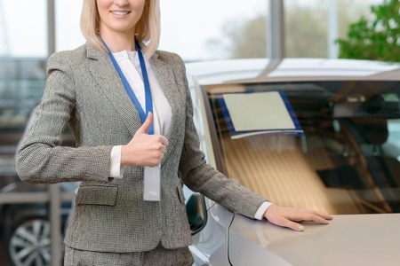 sales representative: Young attractive sales representative is showing thumbs up while presenting selected car. Stock Photo