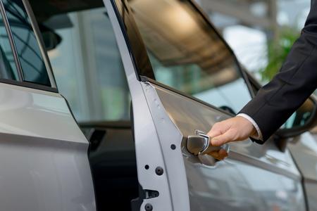 cerrar la puerta: Primer plano de la mano del hombre que alcanza hacia fuera y la apertura de una puerta de coche. Foto de archivo