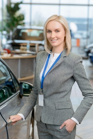 sales clerk: Shoving a vehicle. Young attractive female sales clerk is smiling while holding a door handle.