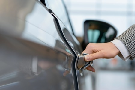 car door: Close up of woman hand reaching out and opening a car door.
