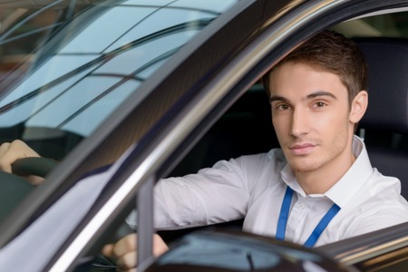 drivers seat: Handsome young salesman looks good and confident while sitting at drivers seat.