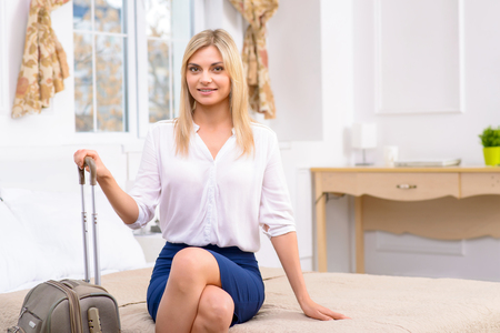 just arrived: Just arrived. Attractive young woman sitting at the edge of bed in her hotel room. Stock Photo