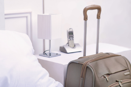 holidays vacancy: Travelers necessity. Big packed travelers suitcase is standing beside the bed table in hotel room Stock Photo