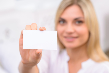 oneself: Presenting oneself. Appealing young woman reaching out to present her business card.