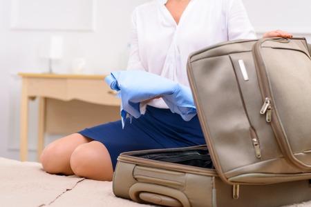 パックの時間。若い女性は、ベッドの上に座って、彼女のバッグを梱包します。