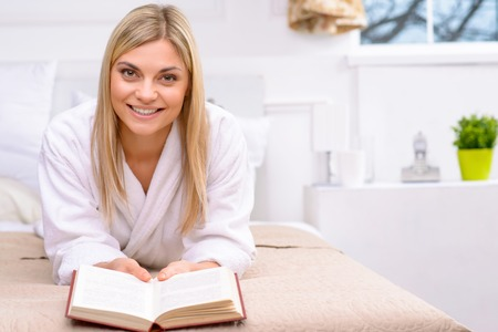 appealing: Leisure time. Young appealing woman is lying in bed and reading her book.