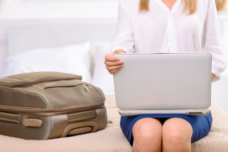 resident: Last minute check. Good-looking female hotel resident with her suitcase packed is sitting on bed and using laptop.