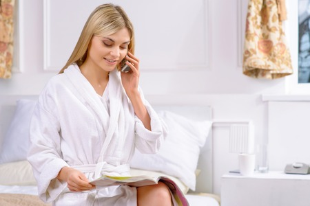appealing: Ordering room service. Appealing young woman sitting on bed and ordering room service over the phone.