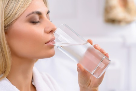 still water: Healthy liquid. Appealing young woman drinking cold still water from a glass. Stock Photo