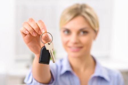 give out: This is your room key. Appealing young receptionist reaching out to give a key to the customer. Stock Photo