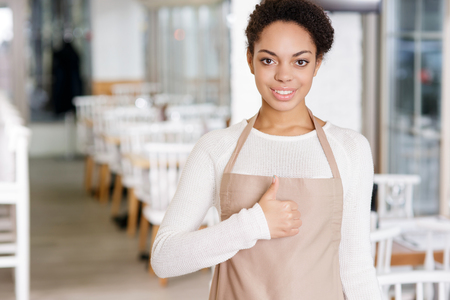 hospitality staff: Ready to work. Attractive young waitress looking optimistic while showing thumbs up.